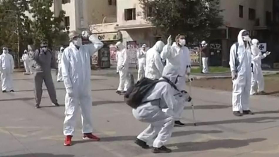 Grupo de manifestantes con overoles blancos protestó a un costado de Plaza Baquedano