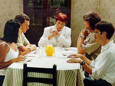 Daniela Lhorente sentada en la mesa junto a Marés González y otros actores