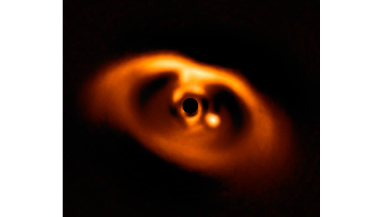 El punto de luz es el planeta en formación. El círculo negro es la estrella que orbita