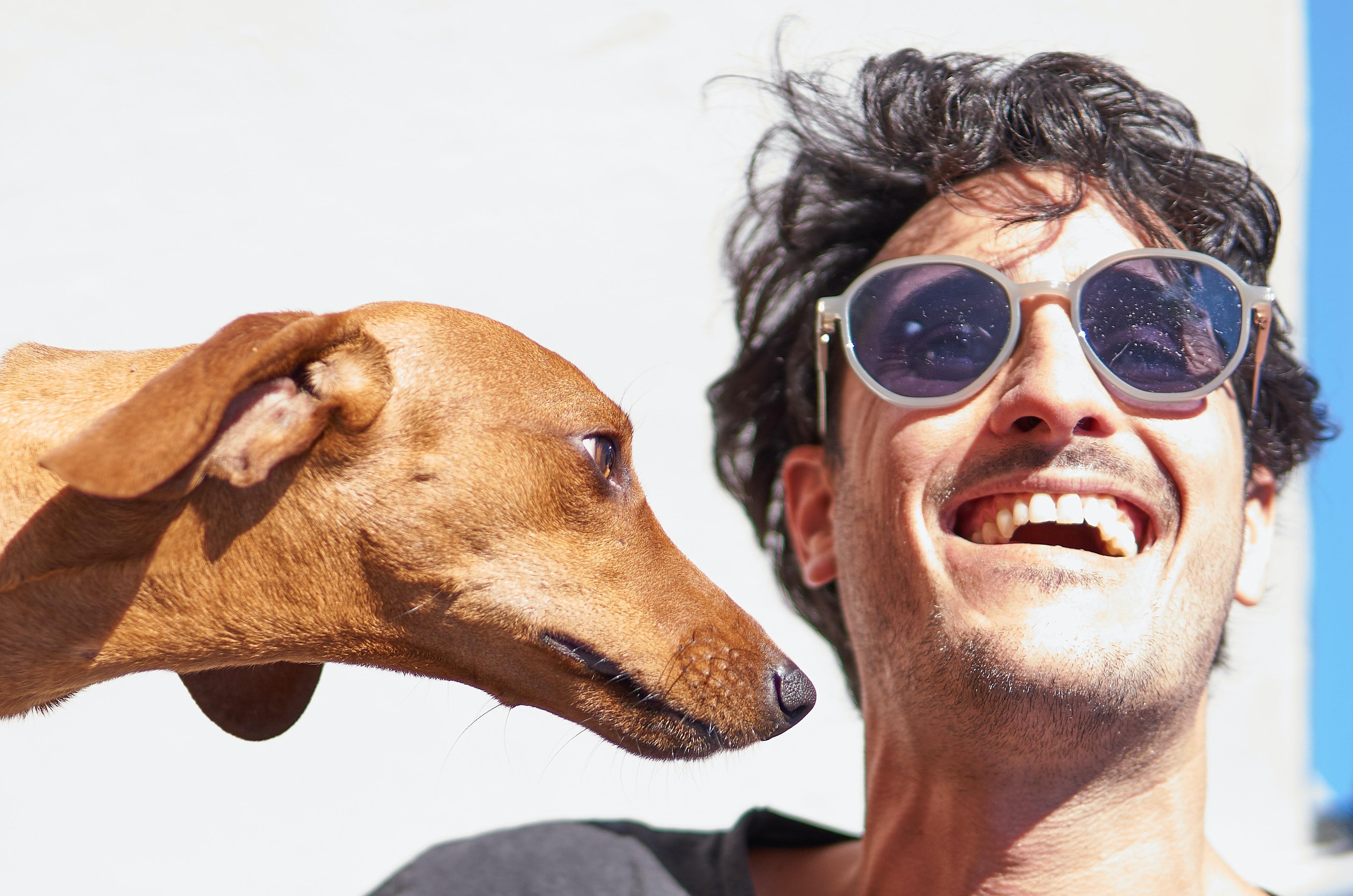 Hombre joven sonríe mientras mira al sol, lo acompaña su perro