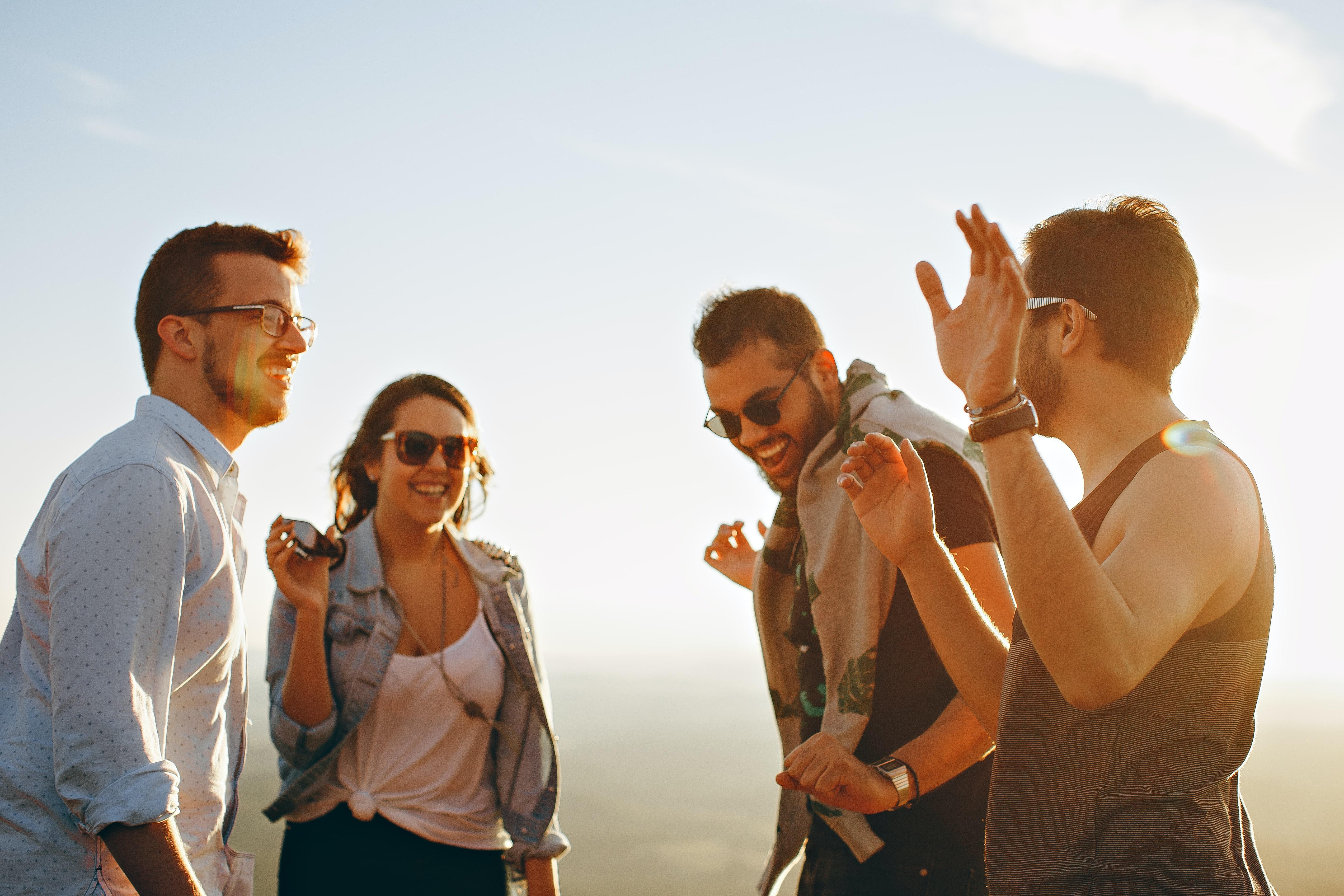 Cuatro personas sonriendo, riendo, pasando un buen rato al aire libre