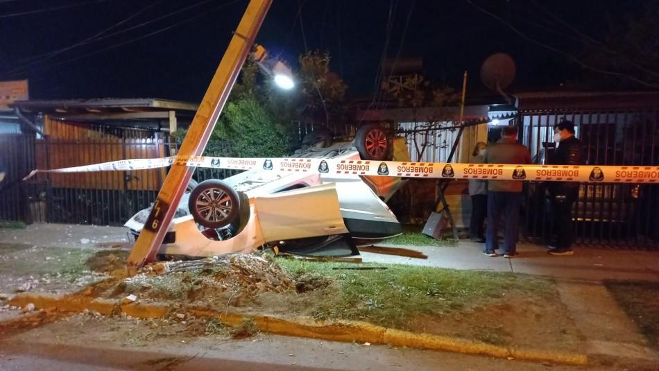 Conductor choca con poste de luz, vuelca su vehículo e impacta con una casa en Peñalolén